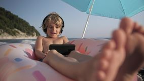 Cute child listening music on smart phone and singing on beach