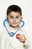 Child Listening to Heartbeat with a Stethoscope. A three year old child is listening to his heartbeat with a toy stethoscope Stock Photo