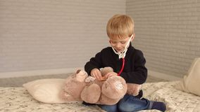 Child listening to heartbeat of teddy bear with stethoscope in a bedroom.