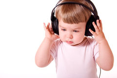 Child listening to the music. Little girl listening to music in the headphones. Studio shot, isolated on white background royalty free stock photography