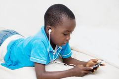 Child listening to music. This child focused on the mobile phone, listening to music with headphones Royalty Free Stock Photos