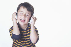 Child listening to music. With headphones Royalty Free Stock Images