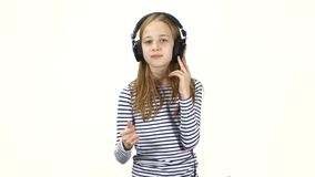 Child listens music in headphones and snaps fingers into rhythm stock footage