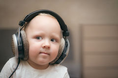 Child listens to music on headphones. Little boy listening to music with big headphones with a smile Royalty Free Stock Photography