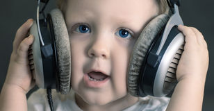 Child listens to music on headphones. Little boy listening to music with big headphones with a smile Royalty Free Stock Images