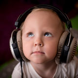 Child listens to music on headphones. Little boy listening to music with big headphones with a smile Royalty Free Stock Photos