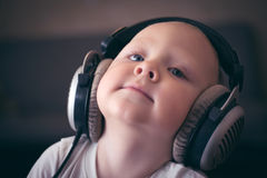 Child listens to music on headphones. Little boy listening to music with big headphones with a smile stock photo