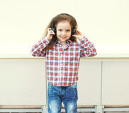 Child listens to music in headphones over white Royalty Free Stock Photos