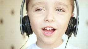 A child listens to music through headphones and sings.