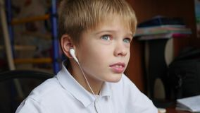 The child listens to music on smartphone in the headphones and hops head in home