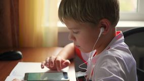 The child listens to music on smartphone in the headphones making lessons stock footage