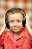 The child listens to music via earphones Royalty Free Stock Images