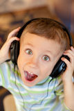 The child listens to music via earphones Royalty Free Stock Photos
