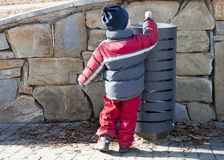 Child and litter or waste bin. Small child putting a waste or litter in an street rubbish can or bin stock photo