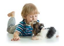Child little boy kissing puppy dog. Isolated on white background. stock image