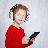 Child little Boy listening to music or watching movie with headp Stock Photo