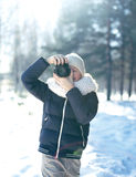 Child little boy photographer takes picture on the digital camera outdoors in winter sunny day over blurred forest backgroun Stock Photos
