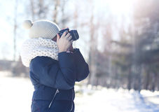 Child little boy photographer takes picture on the digital camera outdoors in winter sunny day over blurred forest background Royalty Free Stock Photos