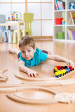 Child little boy playing with wooden railway on the floor. Kid little boy playing with wooden railway on the floor Stock Photo
