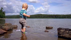Child little boy is standing in a forest lake and playing with stones that he picks up from the bottom of the lake stock video
