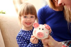 Child little girl arm putting coins into piggybank. Child little girl arm putting pin money coins into happy pink faced piglet slot portrait. Making effective Royalty Free Stock Image