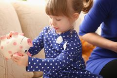 Child little girl arm putting coins into piggybank. Child little girl arm putting pin money coins into happy pink faced piglet slot portrait. Making effective Stock Photos