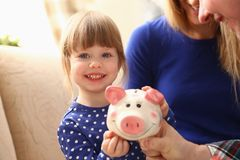 Child little girl arm putting coins into piggybank. Child little girl arm putting pin money coins into happy pink faced piglet slot portrait. Making effective Royalty Free Stock Photography