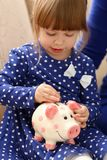 Child little girl arm putting coins into piggybank. Child little girl arm putting pin money coins into happy pink faced piglet slot portrait. Making effective Stock Photography