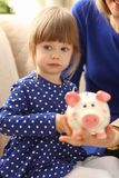 Child little girl arm putting coins into piggybank. Child little girl arm putting pin money coins into happy pink faced piglet slot portrait. Making effective Royalty Free Stock Images