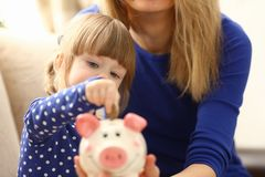 Child little girl arm putting coins into piggybank. Child little girl arm putting pin money coins into happy pink faced piglet slot portrait. Making effective Stock Images