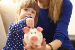 Child little girl arm putting coins into piggybank. Child little girl arm putting pin money coins into happy pink faced piglet slot portrait. Making effective Royalty Free Stock Photos