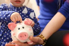 Child little girl arm putting coins into piggybank. Child little girl arm putting pin money coins into happy pink faced piglet slot closeup. Making effective Stock Images