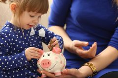 Child little girl arm putting coins into piggybank. Child little girl arm putting pin money coins into happy pink faced piglet slot closeup. Making effective Royalty Free Stock Images