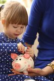 Child little girl arm putting coins into piggybank. Child little girl arm putting pin money coins into happy pink faced piglet slot portrait. Making effective Stock Photo