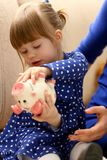 Child little girl arm putting coins into piggybank. Child little girl arm putting pin money coins into happy pink faced piglet slot portrait. Making effective Royalty Free Stock Photo