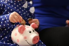 Child little girl arm putting coins into piggybank. Child little girl arm putting pin money coins into happy pink faced piglet slot closeup. Making effective Stock Photos
