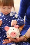 Child little girl arm putting coins into piggybank. Child little girl arm putting pin money coins into happy pink faced piglet slot closeup. Making effective Royalty Free Stock Image