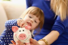 Child little girl arm putting coins into piggybank. Child little girl arm putting pin money coins into happy pink faced piglet slot closeup. Making effective Stock Photo
