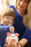 Child little girl arm putting coins into piggybank. Child little girl arm putting pin money coins into happy pink faced piglet slot closeup. Making effective Royalty Free Stock Photography