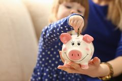 Child little girl arm putting coins into piggybank. Child little girl arm putting pin money coins into happy pink faced piglet slot closeup. Making effective Royalty Free Stock Photo