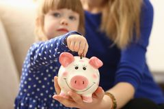 Child little girl arm putting coins into piggybank. Child little girl arm putting pin money coins into happy pink faced piglet slot closeup. Making effective Stock Photography
