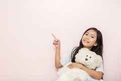Child little girl asian thai nationality with white toy teddy be. Ar over pink wall background pointing to corner Royalty Free Stock Images