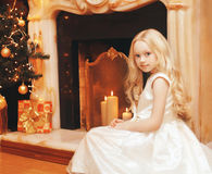 Child little girl in dress near christmas tree and fireplace home Royalty Free Stock Photo