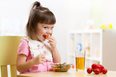 Child little girl eating healthy vegetables Royalty Free Stock Images