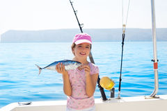 Child little girl fishing in boat holding little tunny fish catc Royalty Free Stock Photo
