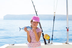 Child little girl fishing in boat holding little tunny fish catc. Child little girl fishing in boat holding little tunny tuna fish catch with rod and trolling Stock Photo