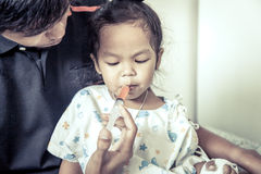 Child little girl gets medicine with a syringe in her mouth Royalty Free Stock Photography