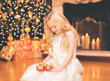Child little girl with gift box near christmas tree and fireplace home Royalty Free Stock Image