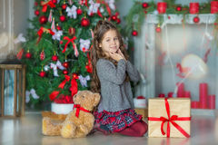 Child little girl with gift box near christmas tree and fireplace at home Stock Photos
