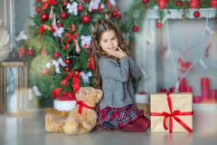 Child little girl with gift box near christmas tree and fireplace at home Stock Photo